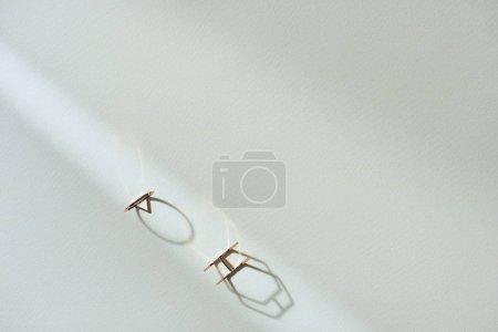 Photo pour Vue de dessus de deux anneaux de luxe belle sur une surface blanche avec soleil - image libre de droit