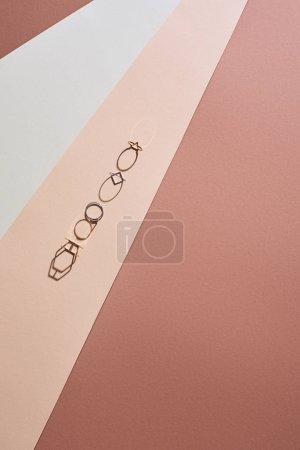 Foto de Vista superior de hermosos anillos de oro en la superficie blanca y beige - Imagen libre de derechos