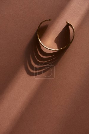 Photo for Top view of beautiful luxury bracelet on brown surface with sunlight - Royalty Free Image