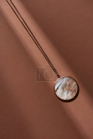 top view of beautiful round locket with marble on brown surface with sunlight