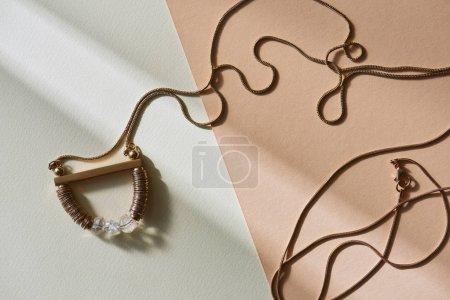 Photo pour Vue de dessus de belle élégance collier sur surface blanche et beige avec lumière du soleil - image libre de droit