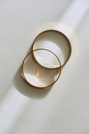 Photo for Top view of two beautiful golden rings on white surface with sunlight - Royalty Free Image