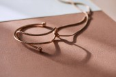 selective focus of beautiful luxury necklace on white and beige surface with sunlight