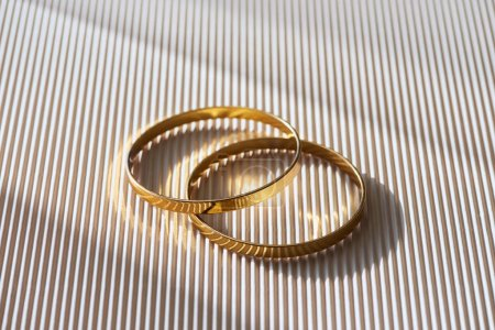 close up of beautiful luxury wedding rings on striped white surface with sunlight