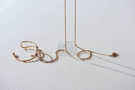 beautiful golden necklace on striped white surface with sunlight