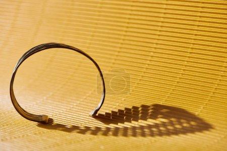 Photo for Beautiful stylish bracelet on yellow striped surface - Royalty Free Image