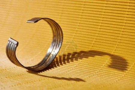 beautiful golden bracelet on yellow striped surface