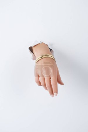 cropped image of woman holding hand with beautiful luxury bracelet through white paper