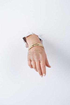 Foto de Recortar imagen de mujer de la mano con la pulsera de bella de lujo a través del libro blanco - Imagen libre de derechos