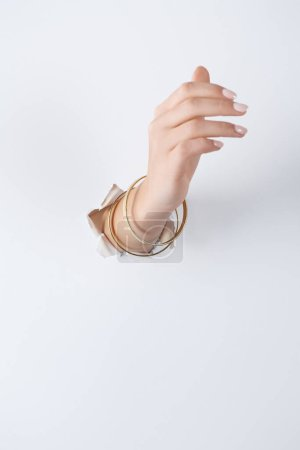 cropped of image woman holding hand with beautiful bracelets through white paper