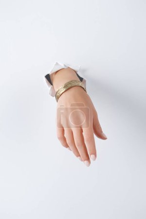 Photo for Cropped image of woman holding hand with beautiful golden bracelet through white paper - Royalty Free Image