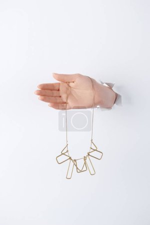 cropped image of woman holding hand with beautiful golden necklace through white paper