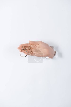 cropped image of woman holding hand with beautiful round golden earrings through white paper