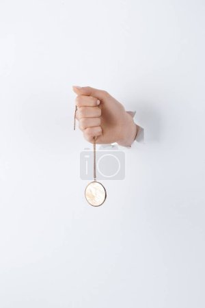 cropped image of woman holding hand with stylish round locket with marble through white paper