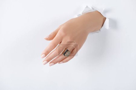 cropped image of woman holding hand with beautiful luxury ring through white paper