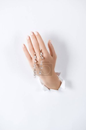 cropped image of woman holding hand with beautiful bracelet with diamonds through white paper