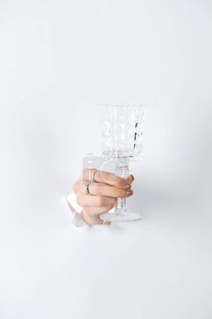 cropped image of woman holding glass in hand with beautiful rings through white paper