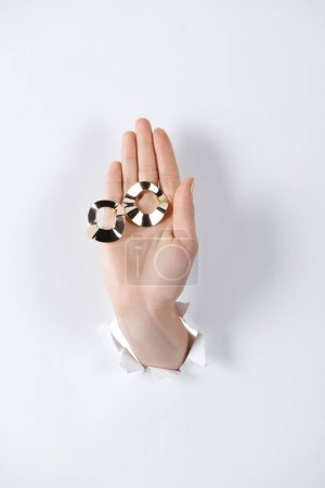 cropped image of woman holding hand with beautiful black and white earrings through white paper