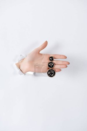 Foto de Recortar imagen de mujer de la mano con el pendiente precioso de lujo con diamantes a través del libro blanco - Imagen libre de derechos