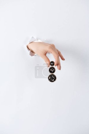 cropped image of woman holding hand with beautiful expensive earring with shiny diamonds through white paper