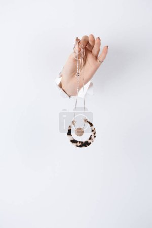 cropped image of woman holding hand with beautiful stylish necklace through white paper