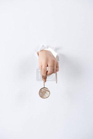 Photo pour Image recadrée de main tenue femme avec beau luxe rond médaillon en marbre par le livre blanc - image libre de droit