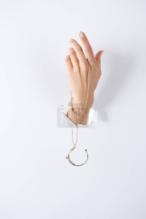 Foto de Recortar imagen de mujer de la mano con el collar de lujo hermosa a través del libro blanco - Imagen libre de derechos