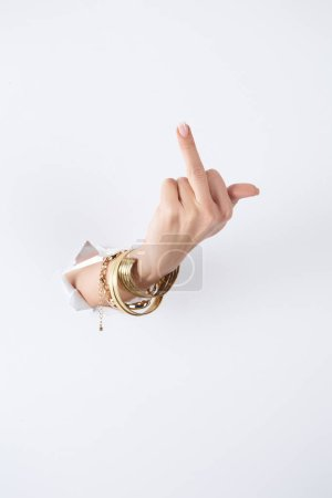 cropped image of woman holding hand with bracelets through white paper and showing middle finger
