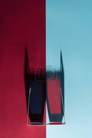 Photo pour Vue de carton de dessus des lunettes 3d avec les ombres verticales sur fond bleu et bordo - image libre de droit