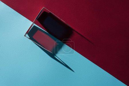 Draufsicht auf 3D-Brillen mit langem Schatten auf blauem und bordofarbenem Hintergrund
