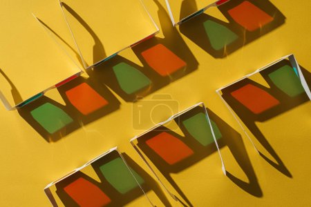 top view of cardboard 3d glasses in two rows with shadows on yellow background