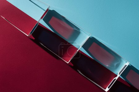 top view of 3d glasses in row with long shadows on blue and bordo background