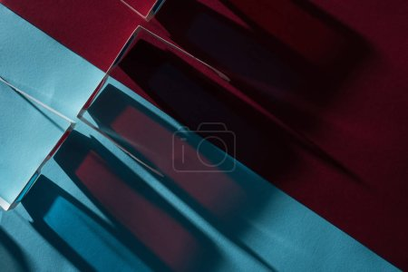 top view of 3d glasses with long shadows on blue and bordo background