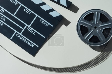 Photo for Top view of clapperboard and film reel with cinema tape on grey background - Royalty Free Image