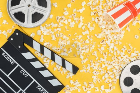 Photo for Film reels, clapperboard and overturned striped bucket with popcorn isolated on yellow - Royalty Free Image