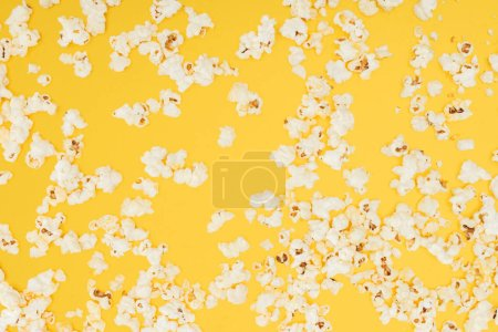 top view of crunchy scattered popcorn isolated on yellow