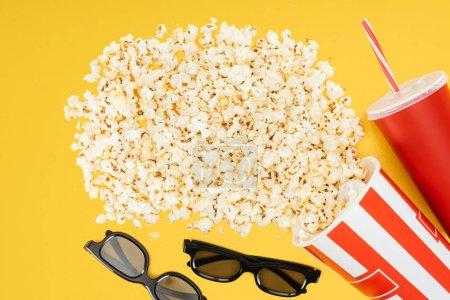 Photo pour Vue du dessus des verres 3d, tasse jetable rouge avec paille et seau rayé renversé avec pop-corn isolé sur jaune - image libre de droit