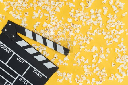 Photo for Top view of clapperboard and fresh tasty popcorn isolated on yellow - Royalty Free Image
