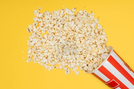 top view of overturned striped bucket with popcorn isolated on yellow