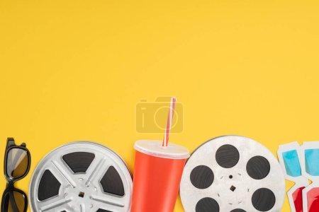 Photo pour Lunettes 3D, bobines de film et tasse jetable rouge avec paille isolée sur jaune - image libre de droit