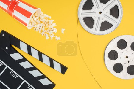 Photo for Top view of clapperboard, overturned striped bucket with popcorn and film reels with cinema tape isolated on yellow - Royalty Free Image