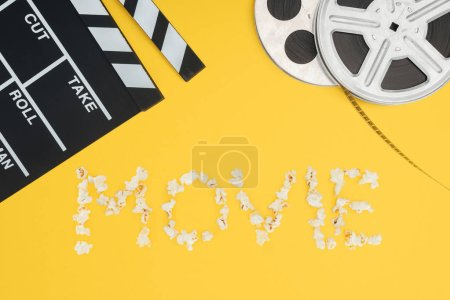 """clapperboard, film reels and """"movie"""" lettering made with popcorn isolated on yellow"""