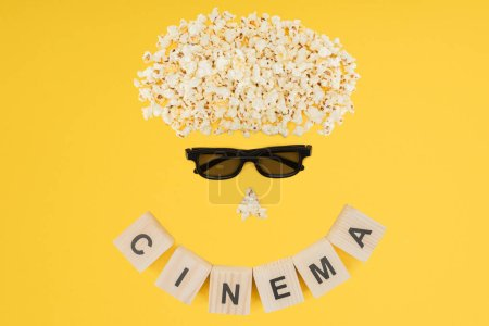 "stereoscopic 3d glasses, popcorn and cubes with ""cinema"" lettering isolated on yellow"