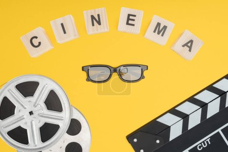 """wooden cubes with """"cinema"""" lettering, clapperboard, film reels and stereoscopic 3d glasses isolated on yellow"""
