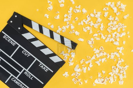 Photo for Top view of cinema clapperboard and crunchy popcorn isolated on yellow - Royalty Free Image