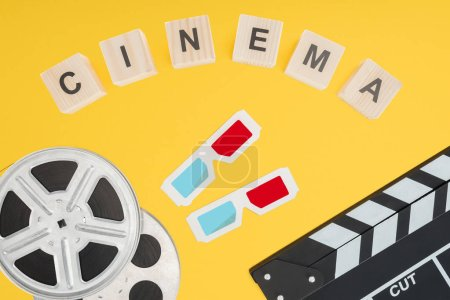 "cubes with ""cinema"" lettering, 3d glasses, clapperboard and film reels isolated on yellow"
