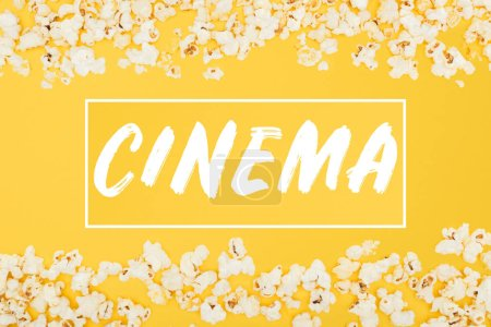"""cinema"" lettering in horizontal frame made of fresh popcorn isolated on yellow"