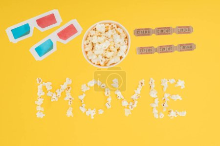 "top view of 3d glasses, bucket with popcorn, cinema tickets and ""movie"" lettering made with popcorn isolated on yellow"
