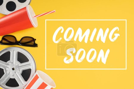 "film reels, 3d glasses, popcorn bucket, red disposable cup with straw and ""coming soon"" lettering isolated on yellow"