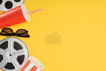 film reels, 3d glasses, popcorn bucket and red disposable cup with straw isolated on yellow